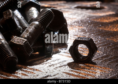 Random artistic pile of threaded bolts and a  hexagonal nut on a sheet steel, backlit, - Stock Photo