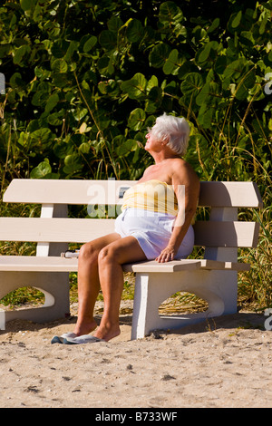 Palm Beach Shores , Florida , mature large elderly gray haired woman asleep in sun sunbathing on bench on sand by - Stock Photo