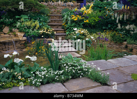 Flagstone steps over pool with mixed herbaceous planting - Stock Photo