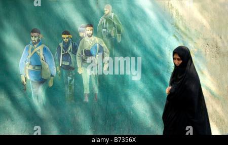 tehran black veil veiled muslim woman walking past anti american martyrs mural by old american embassy in teheran - Stock Photo