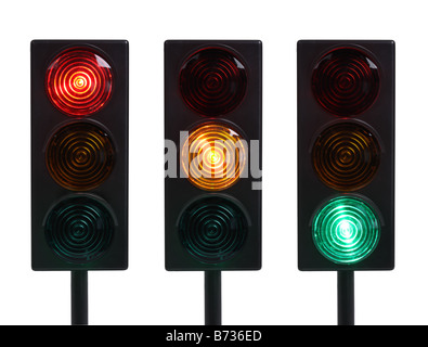 Three traffic lights with red yellow and green lights cut out on white background - Stock Photo