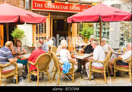 Gibraltar People sitting in sun enjoying drinks at tables on Main Street outside The Gibraltar Arms pub