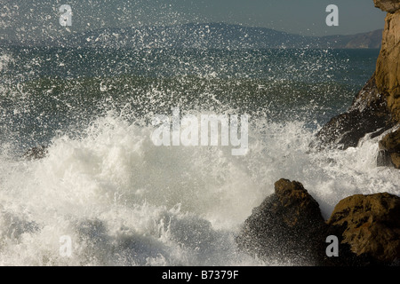 Waves breaking on the rocky Pacific Ocean coast of San Francisco central north California USA - Stock Photo