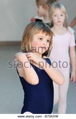 Ballerina holding a bean bag on shoulder in dance class - Stock Photo