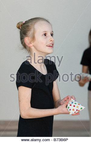 Ballerina holding a bean bag in dance class - Stock Photo