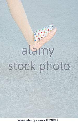 Ballerina balancing a bean bag on her ballet slipper - Stock Photo