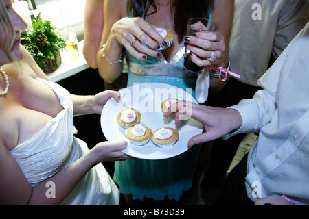 Bride handing wedding cakes to guests at her wedding reception. - Stock Photo