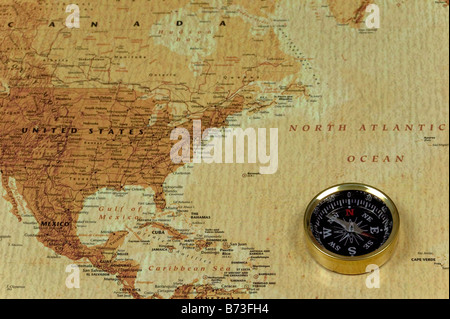 A brss compass on an old map showing the North Atlantic ocean and the United States of America - Stock Photo