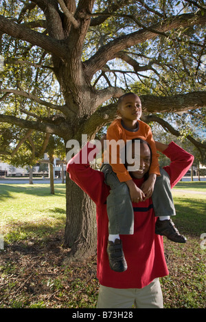 African American father holding son on shoulders in park - Stock Photo