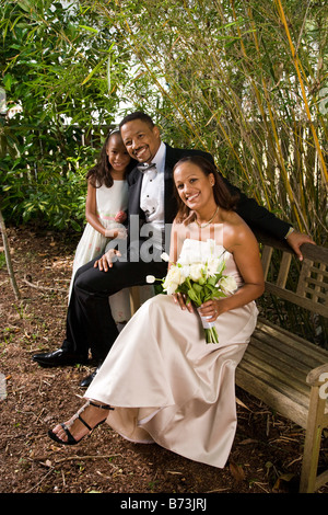 Happy African American bride and groom in outside nature setting with flower girl - Stock Photo