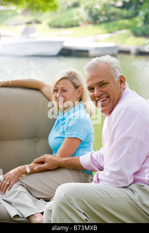 Portrait of middle-aged couple sitting on sofa outside, with boats in background - Stock Photo