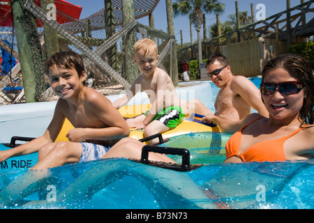 Side view of young family having fun at water park floating on innertubes - Stock Photo