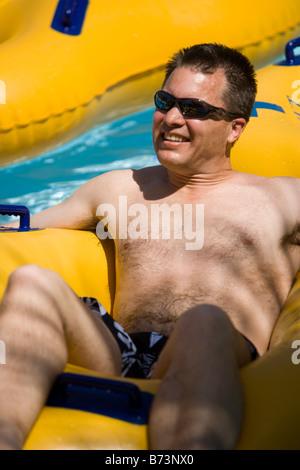 Man relaxing on innertube on lazy river in water park - Stock Photo