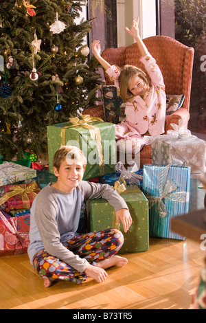Children sitting next to Christmas tree and presents - Stock Photo