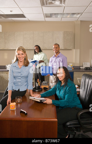 Portrait of four multi-racial office workers meeting - Stock Photo