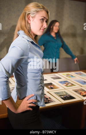 Young female office workers reviewing marketing material in boardroom - Stock Photo