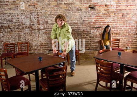 Multi-ethnic teenage couple apart in restaurant - Stock Photo