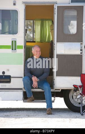 Senior man sitting in doorway of RV camper - Stock Photo