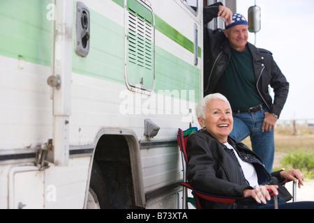 Happy senior couple outside RV camper - Stock Photo