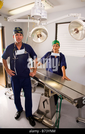 Two veterinarians standing in empty examination or operating room - Stock Photo