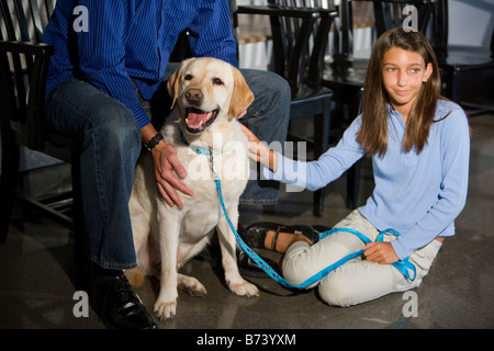 Father and daughter in waiting room of vet clinic with pet dog - Stock Photo