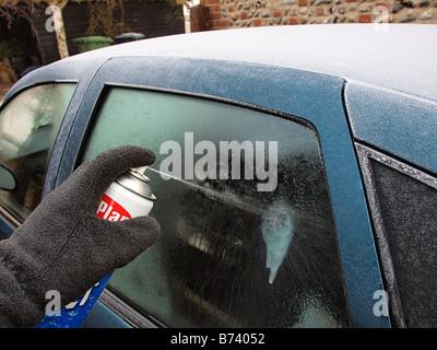 MALE SPRAYING DEICER ONTO ICE ON REAR WINDSCREEN OF CAR HAPPISBURGH NORFOLK EAST ANGLIA ENGLAND UK - Stock Photo