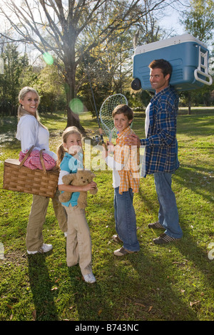 Young happy family carrying picnic basket and cooler in park - Stock Photo