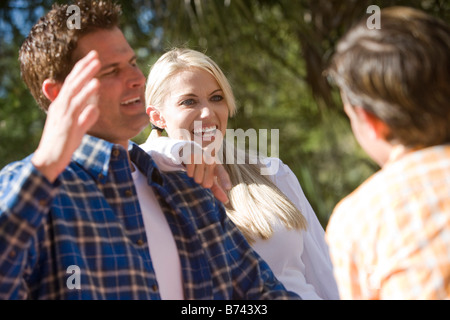 Mother laughing with family outdoors in park - Stock Photo