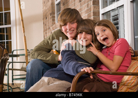 Siblings hugging each other on porch - Stock Photo