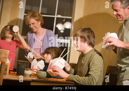 Family eating Chinese takeout for dinner at home - Stock Photo