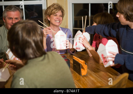 Family eating Chinese takeout together at home - Stock Photo