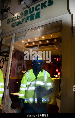 Police with riot shields outside the Israeli embassy.One policeman stands guard outside Starbucks - Stock Photo