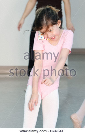 Ballerina balancing a bean bag on shoulder in dance class - Stock Photo