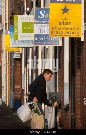 A student moving into a rented house in a street in Exeter with a number of 'To Let' signs - Stock Photo