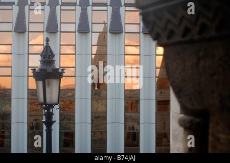 REFLECTION OF A SUNSET OVER THE FISHERMAN S BASTION IN BUDAPEST HUNGARY IN A MODERN GLASS BUILDING - Stock Photo