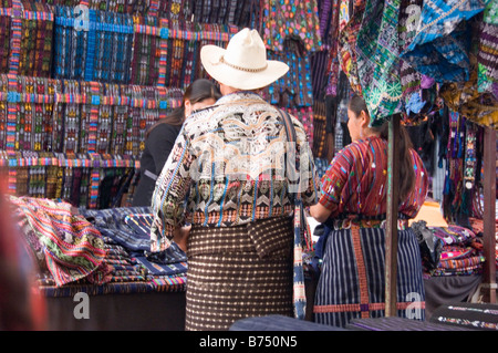 Man and woman in typical traditional dress in front of a market stall selling these clothes. Solola, Guatemala. - Stock Photo