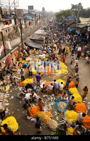 People buy and sell flowers at the colourful Mullick Ghat Flower Market near to the Howrah Bridge in Kolkata, India. - Stock Photo