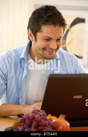 Mann arbeitet zu Hause mit einem Notebook, man working at home on notebook - Stock Photo