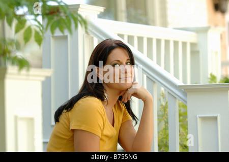 Young woman sitting on steps, Regina, Saskatchewan - Stock Photo