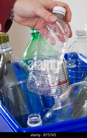 Homemaker adding to blue box full of bottles and cans for recycling - Stock Photo