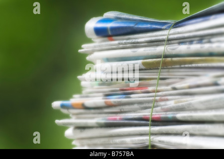 Newspapers tied into a pile for the recycle bin - Stock Photo