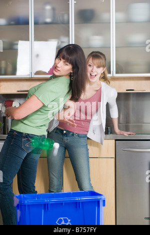 Woman tossing recyling into recycling bin as friend watches, Winnipeg, Manitoba - Stock Photo