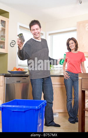 Couple laughing in kitchen as man tosses can into recycling bin, Winnipeg, Canada - Stock Photo