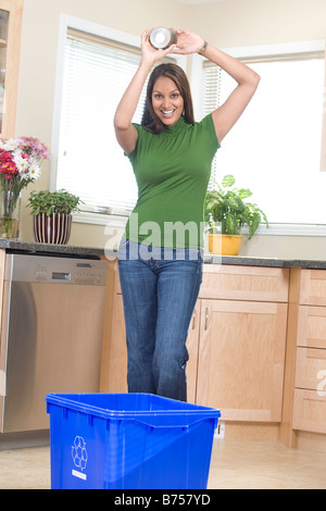 Woman tossing can into recycling box, Winnipeg, Canada - Stock Photo