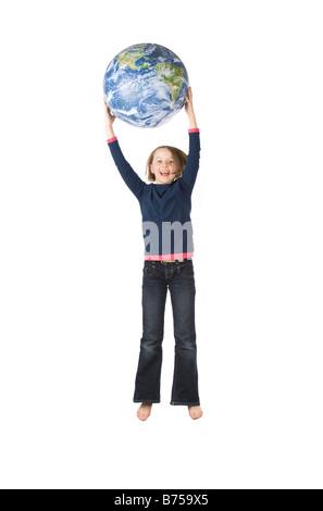 9 year old girl jumping with the globe, Winnipeg, Manitoba - Stock Photo