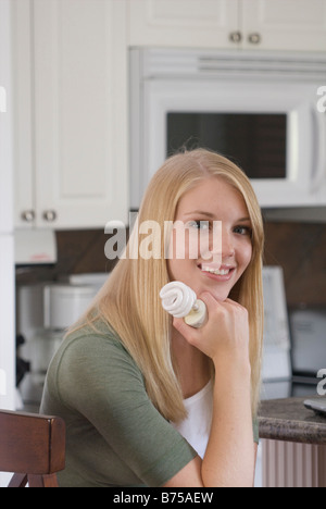 Young woman holding compact fluorescent bulb in kitchen, Brandon, Manitoba, Canada - Stock Photo