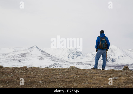 Hiker overlooks snow-capped mountains along the Fish Lake hiking trail outside of Whitehorse, Yukon, Canada - Stock Photo
