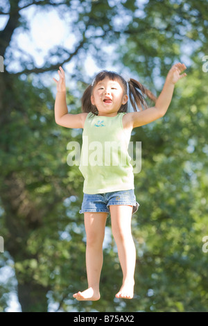6 year old Asian girl jumping, Winnipeg, Manitoba, Canada - Stock Photo