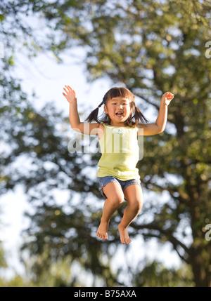 6 year old  Asian girl jumping, Winnipeg, Manitoba, Canada - Stock Photo