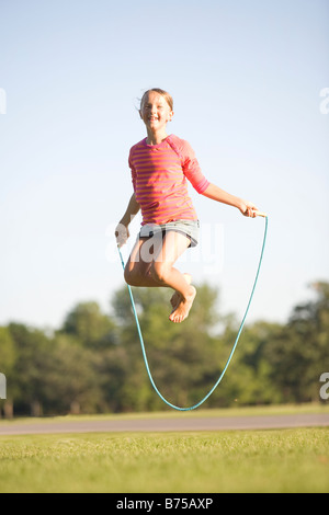 11 year old girl jumps high with skipping rope, Winnipeg, Manitoba, Canada - Stock Photo